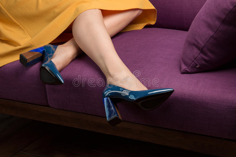 Young girl in a yellow skirt and blue shoes royalty free stock image