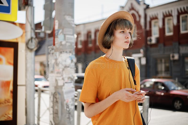 Young girl in a yellow t-shirt and straw hat walks with a backpack along a city street on a summer sunny day royalty free stock images