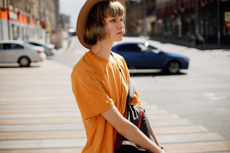 Young girl in a yellow t-shirt and straw hat walks with a backpack along a city street on a summer sunny day.  royalty free stock photos
