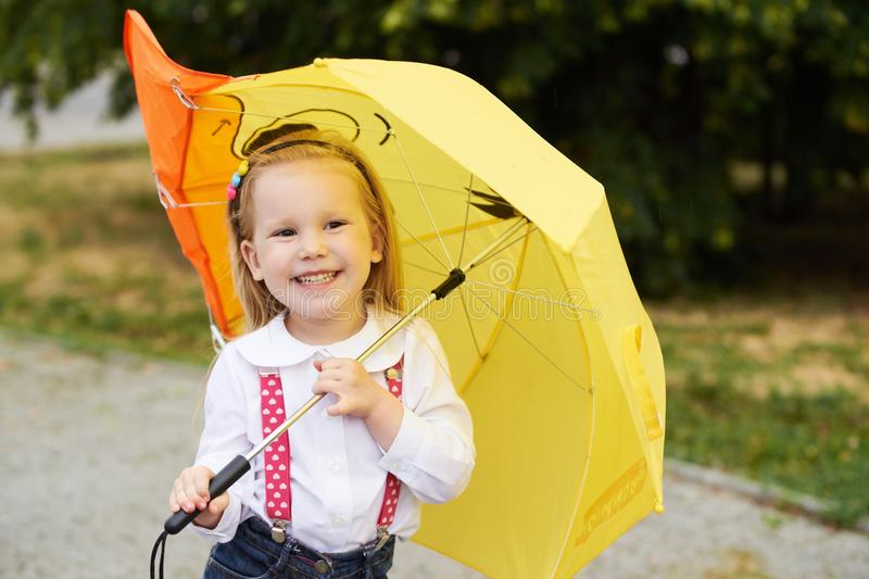 Young girl with yellow umbrella royalty free stock photography