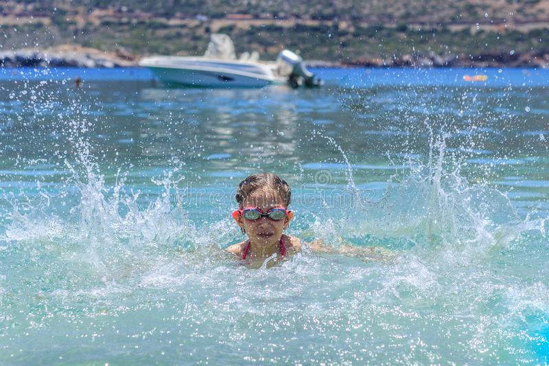 Young girl at yhe sea having fun and splashing water in summer stock photo