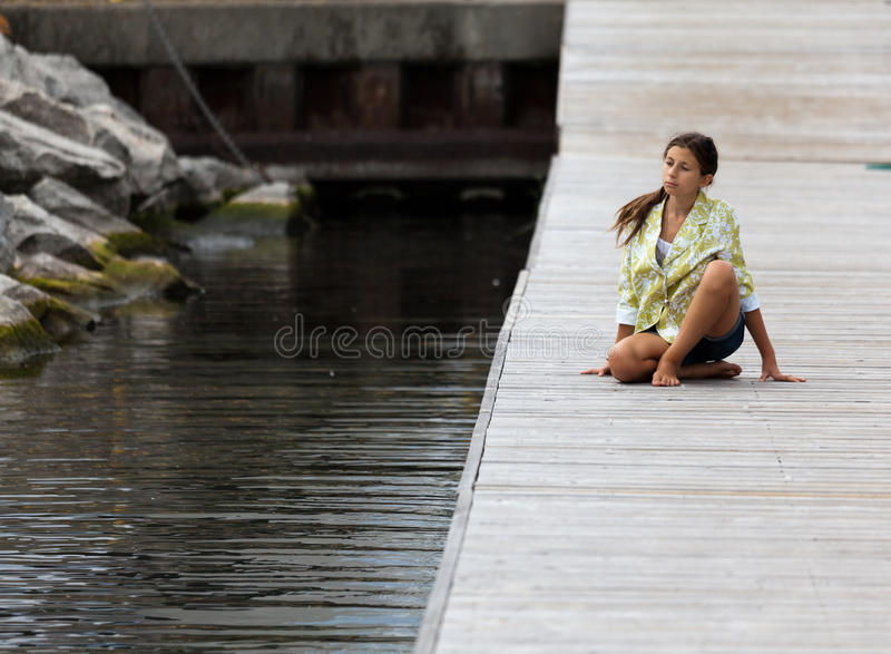 Young Girl In Yoga Posture On A Dock Royalty Free Stock Image