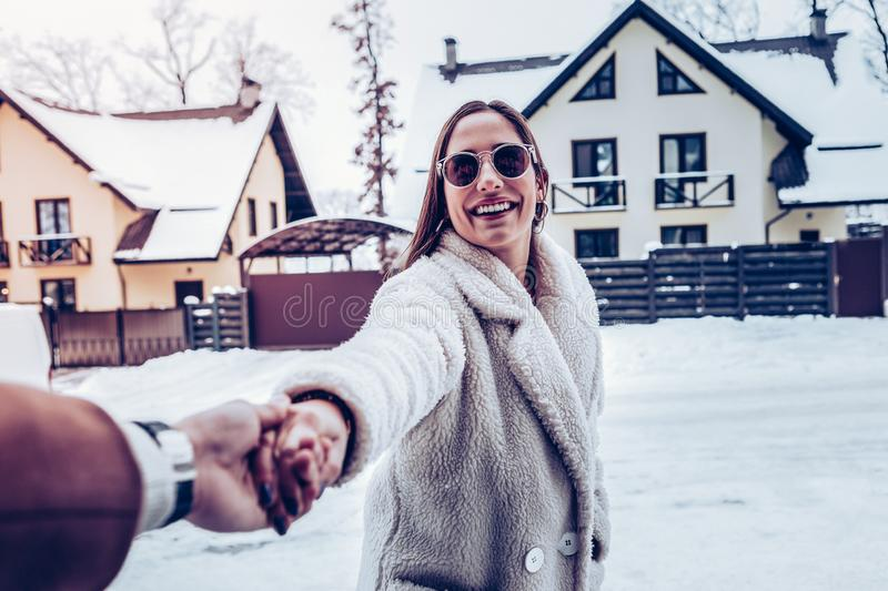 Young girlfriend feeling happy seeing snow walking with her man royalty free stock images