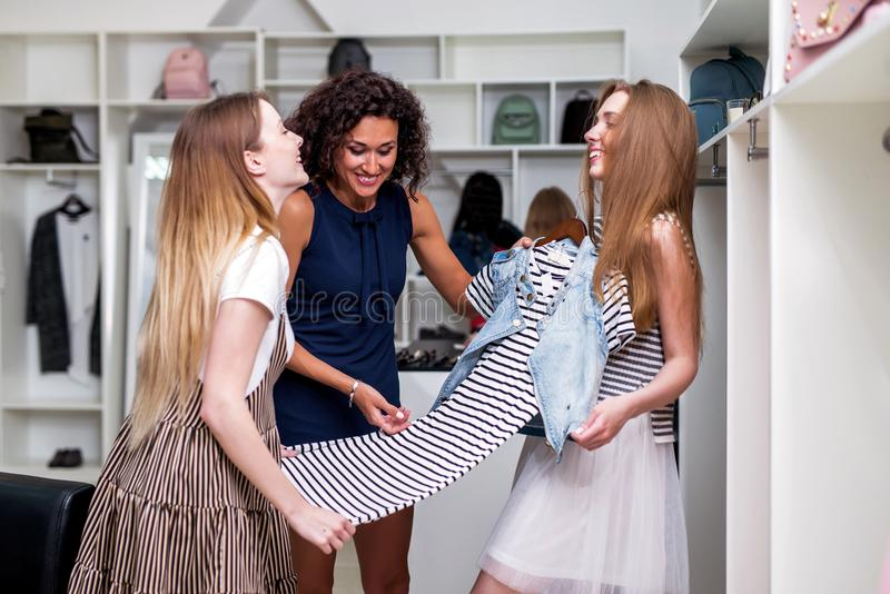 Young girlfriends choosing new clothes together holding, evaluating, discussing a dress in clothing shop.  stock photography
