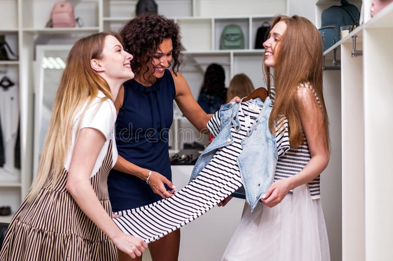 Young girlfriends choosing new clothes together holding, evaluating, discussing a dress in clothing shop.  stock images