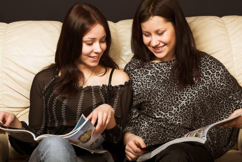 Young girlfriends reading magazine stock photo