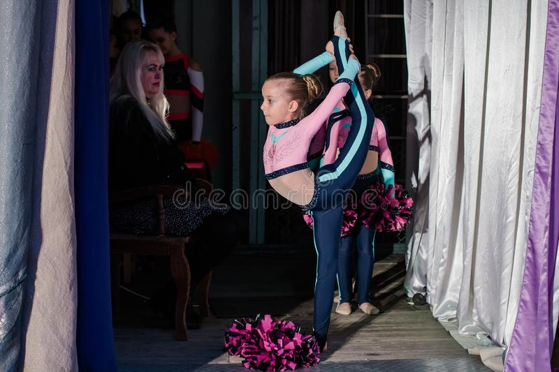 Young girls - athletes are preparing for the show, many young cheerleaders are standing on stage behind the curtain, sportsmen are royalty free stock photography