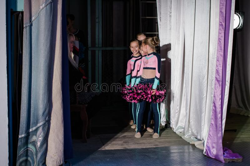 Young girls - athletes are preparing for the show, many young cheerleaders are standing on stage behind the curtain, sportsmen are royalty free stock photos