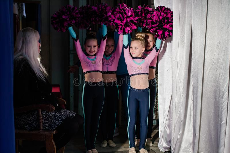 Young girls - athletes are preparing for the show, many young cheerleaders are standing on stage behind the curtain, sportsmen are royalty free stock images