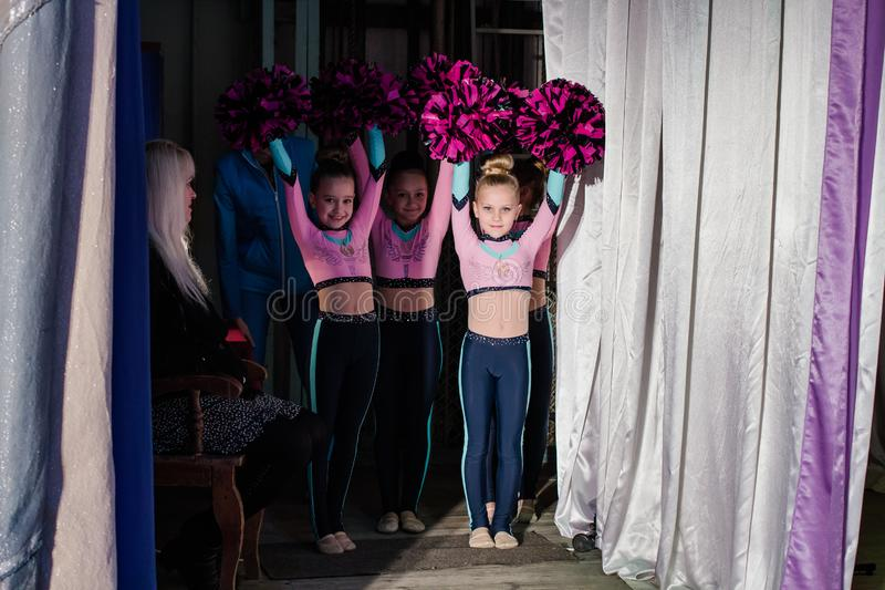 Young girls - athletes are preparing for the show, many young cheerleaders are standing on stage behind the curtain, sportsmen are royalty free stock image
