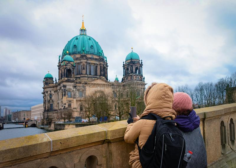 Young girls with backpack taking photos on bridge Berlin Cathedral royalty free stock images