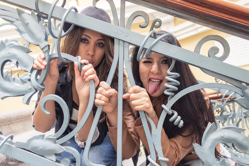 Young girls behind metal railings stock photo
