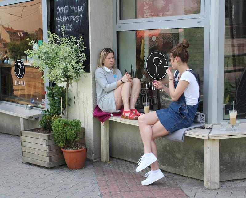 Young girls chatting in front of a coffee house in Bratislava, capital of Slovakia. Meeting friends - two young girls chatting in front of a coffee house in royalty free stock photo