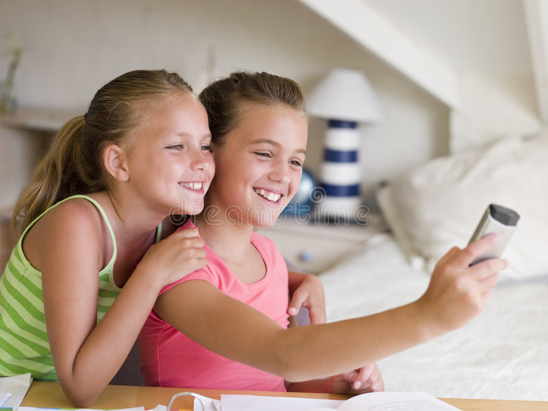 Young Girls Distracted From Their Homework. Playing With A Cellphone stock photo