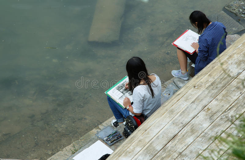 Young girls drawing the houses in Fenghuang royalty free stock photography