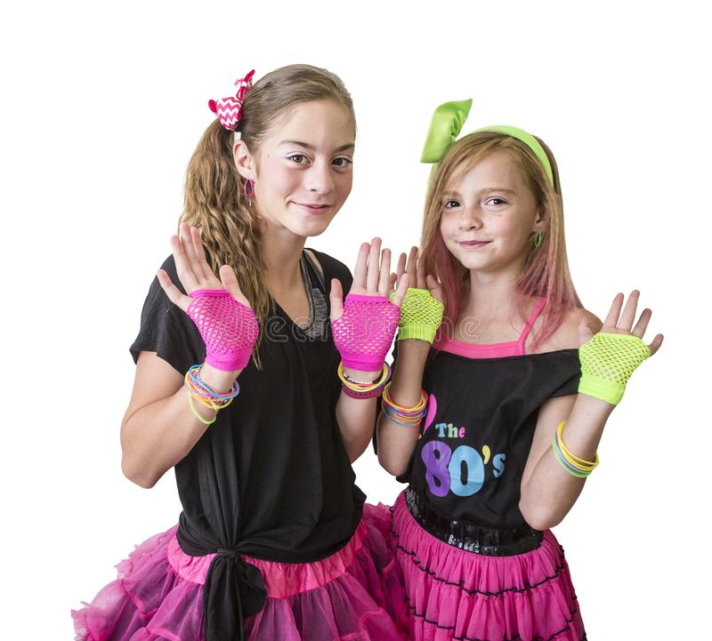 Young girls dressed in retro 80s clothing isolated on a white background. Cute girls dressed in retro 80s decade costumes. Smiling happy girls isolated on a stock photo