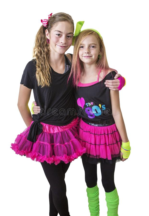 Young girls dressed in retro 80s clothing isolated on a white background. Cute girls dressed in retro 80s decade costumes. Smiling happy girls isolated on a royalty free stock image