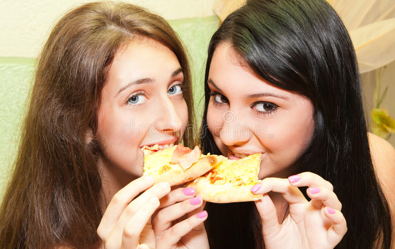 Download Young girls eating pizza stock image. Image of indoors - 20335507