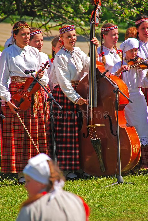 Young girls enjoy playing musical instrument during Latvian outdoor Folk Festival at Turaida field, Latvia royalty free stock images