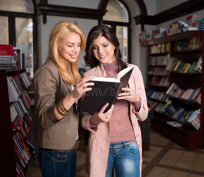 Young Girls Enjoying Reading A Book Stock Image