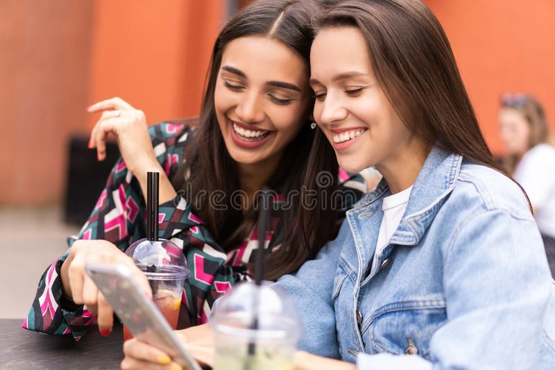 Young girls friends watch something in smartphone. Shocking news. Girls are anxious, scared, surprised. Women and internet news, gossip concept stock photos