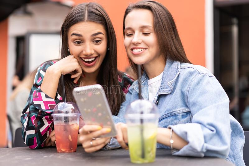 Young girls friends watch something in smartphone. Shocking news. Girls are anxious, scared, surprised. Women and internet news, gossip concept royalty free stock images