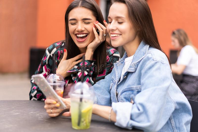 Young girls friends watch something in smartphone. Shocking news. Girls are anxious, scared, surprised. Women and internet news, gossip concept stock image