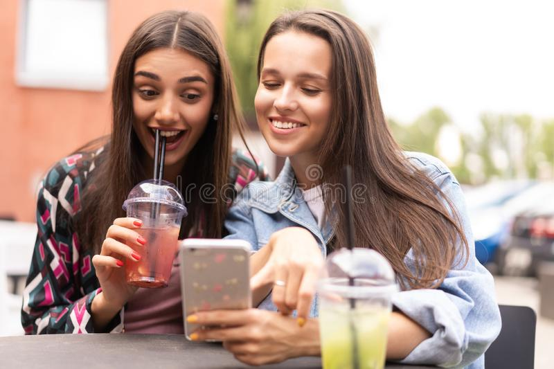 Young girls friends watch something in smartphone. Shocking news. Girls are anxious, scared, surprised. Women and internet news, gossip concept stock images