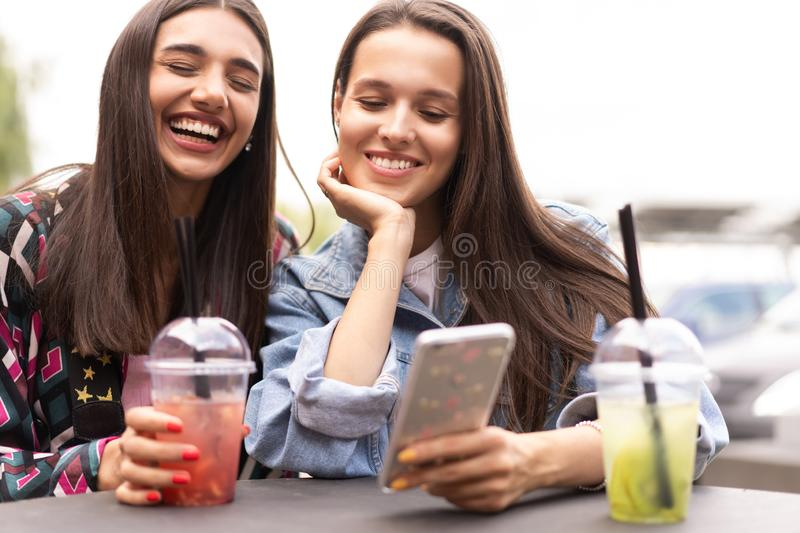 Young girls friends watch something in smartphone. Shocking news. Girls are anxious, scared, surprised. Women and internet news, gossip concept stock photography