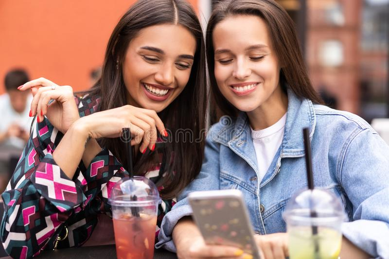 Young girls friends watch something in smartphone. Shocking news. Girls are anxious, scared, surprised. Women and internet news, gossip concept royalty free stock photos