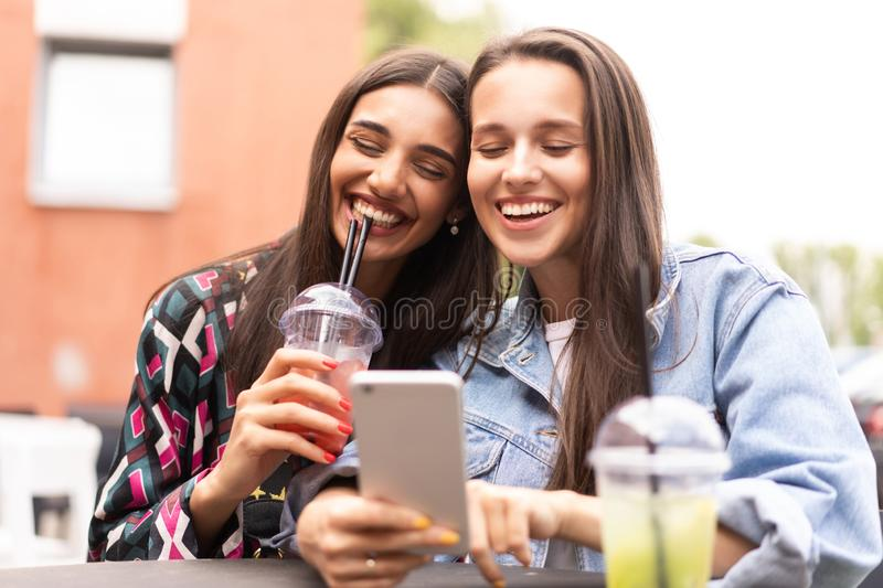 Young girls friends watch something in smartphone. Shocking news. Girls are anxious, scared, surprised. Women and internet news, gossip concept stock photo