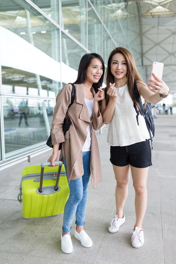 Young girls go travel and taking selfie with mobile phone in Hon. G Kong airport ,beautiful young asian woman stock photography
