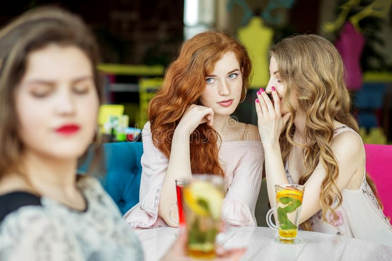 Young girls gossip behind the back of a friend. The concept of lifestyle, gossip, lies, friendship.  stock photography
