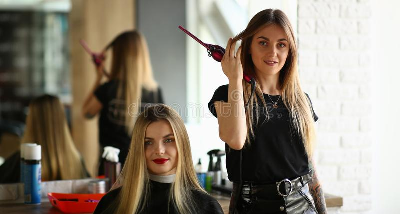 Young Girls Hairdresser and Beauty Salon Client. Hairstylist Holding Curling Iron in Hand. Female Customer Sitting in Studio for Making Haircut. Two Beautiful stock image