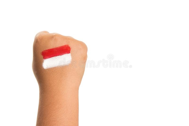 Young girls hand only making a fist with the Indonesian flag painted on her hand. Holiday event Indonesian independence day concept image with copy space for stock images