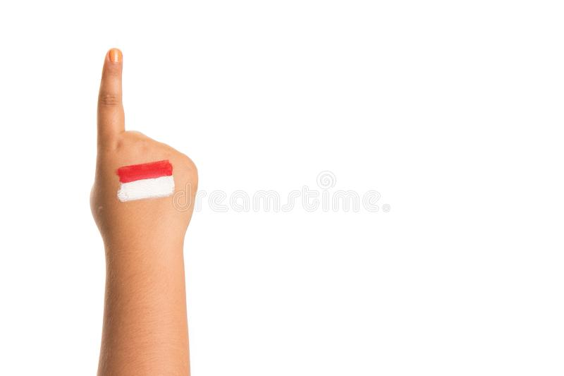 Young girls hand only pointing one finger up `number 1` with the Indonesian flag painted on her hand. Holiday event Indonesian independence day concept image stock photos