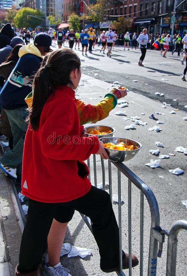Young Girls Handing Snacks to Marathon Runners. New York City, NY USA. Nov 2008. Young girls handing out oranges to runners during the New York City Marathon royalty free stock images