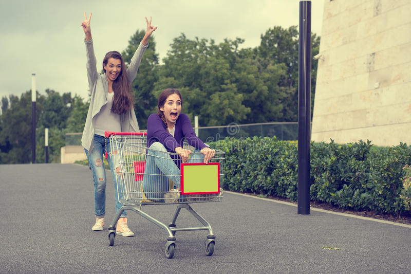 Young girls have fun with the shopping trolley royalty free stock photos