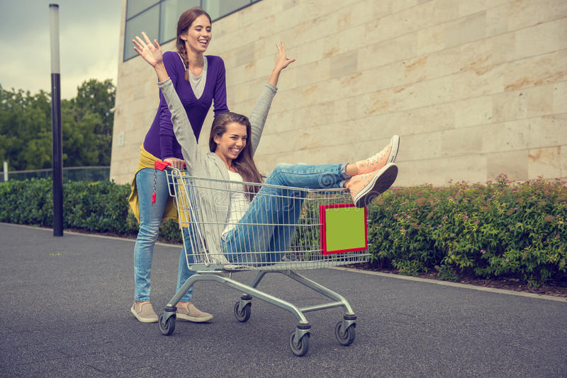 Young girls have fun with the shopping trolley stock photo