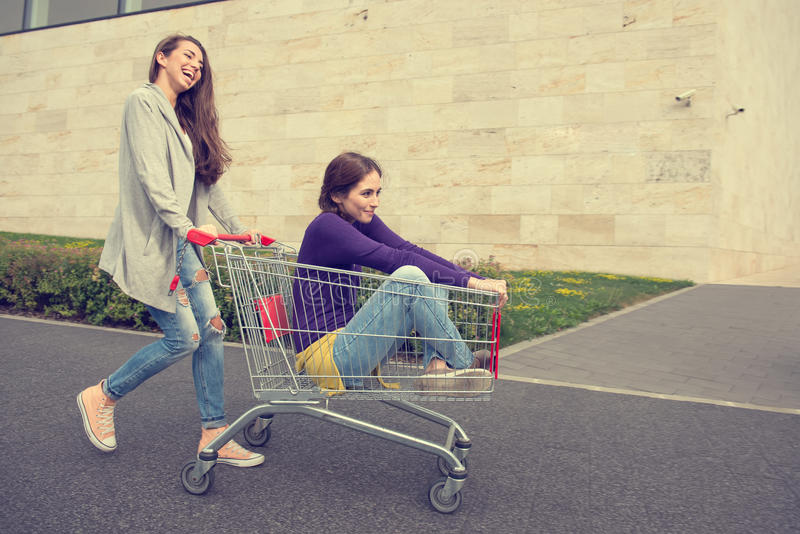 Young girls have fun with the shopping trolley stock images