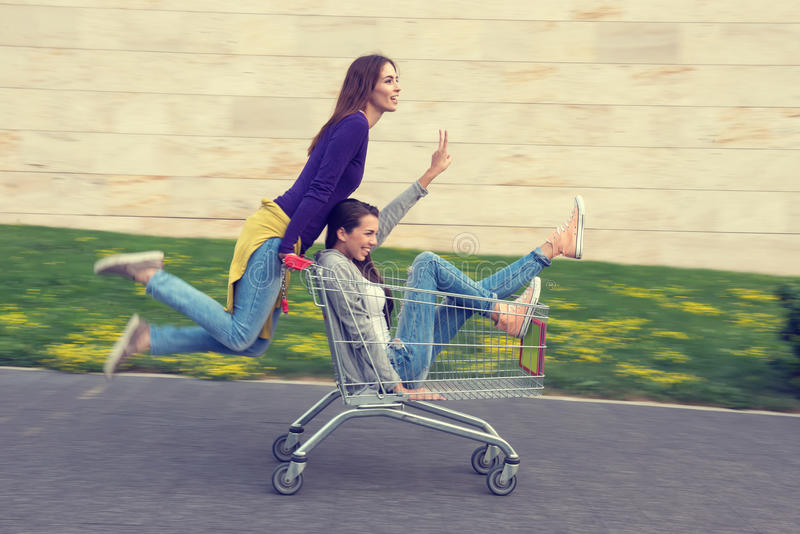 Young girls have fun with the shopping trolley royalty free stock photography