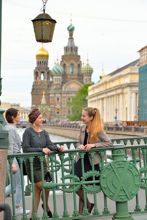 Young girls laughing on the Italian bridge across the Griboyedov royalty free stock photography