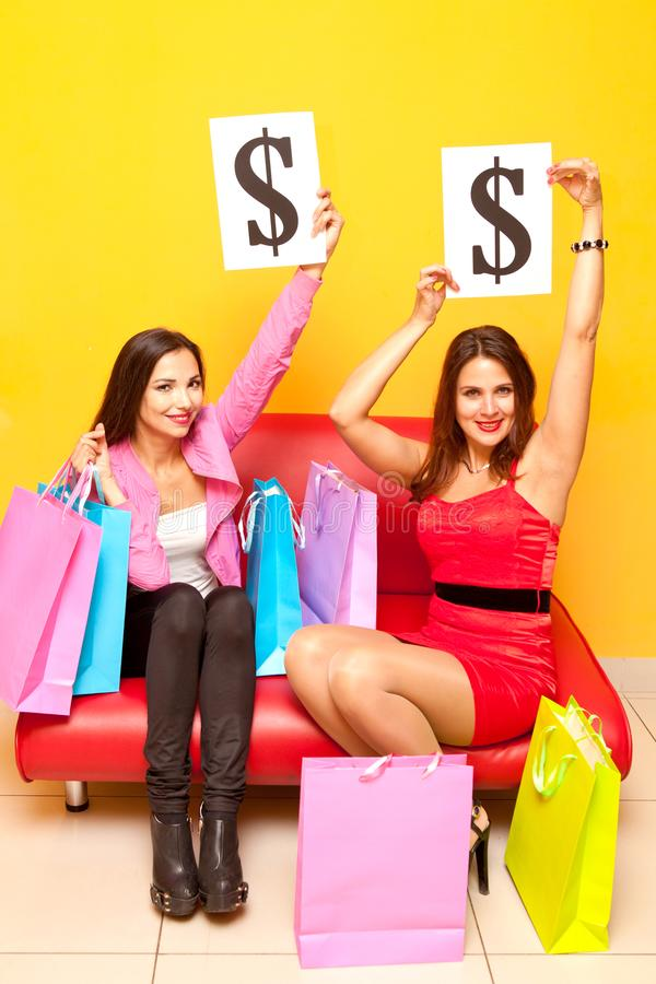 Young girls and a lot of bags in the mall and holding signs dollar royalty free stock photo