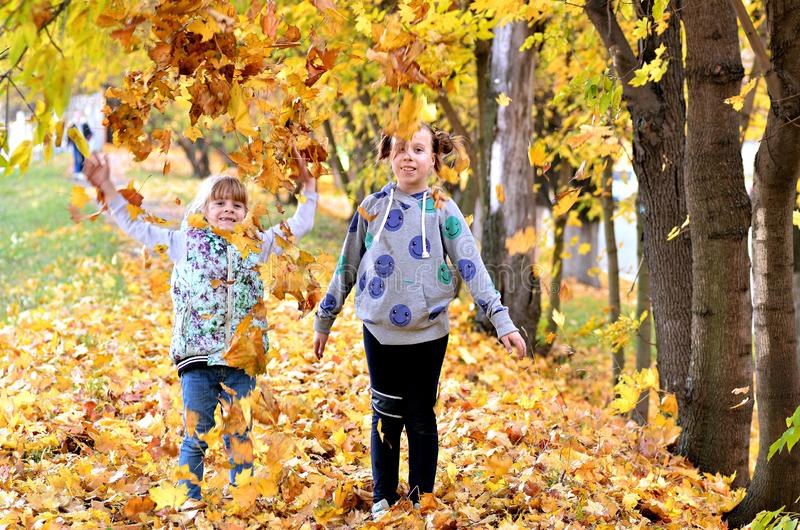 Young girls play outdoors in the autumn season stock photos