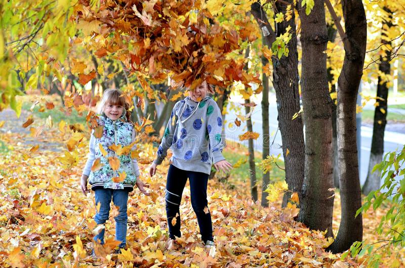 Young girls play outdoors in the autumn season royalty free stock photos