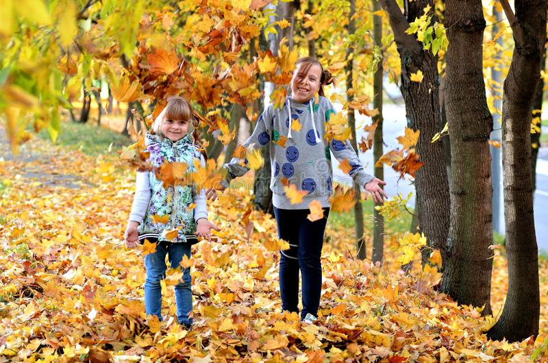 Young girls play outdoors in the autumn season royalty free stock photography