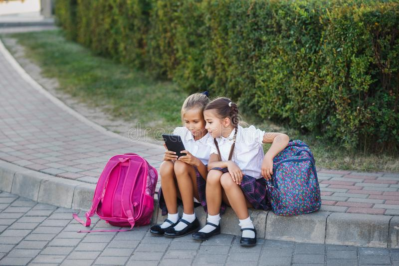 Young girls reading an ebook. Pupils of primary school. Girls with backpacks near building outdoors. Beginning of lessons. First d royalty free stock photography