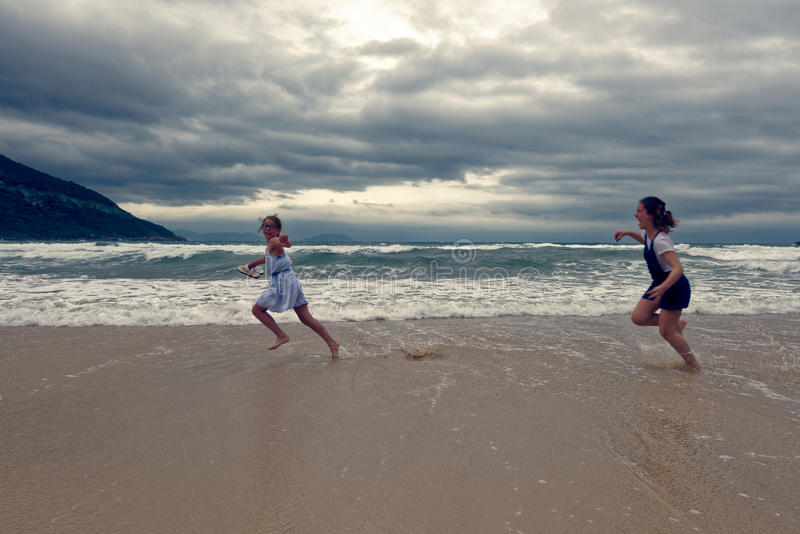 Girls chasing on beach, Vietnam stock photos