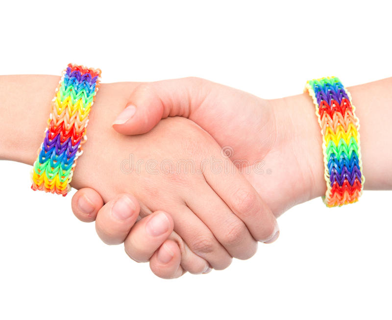 Young girls shaking hands with a bracelet patterned as the rainbow flag. on white stock photos