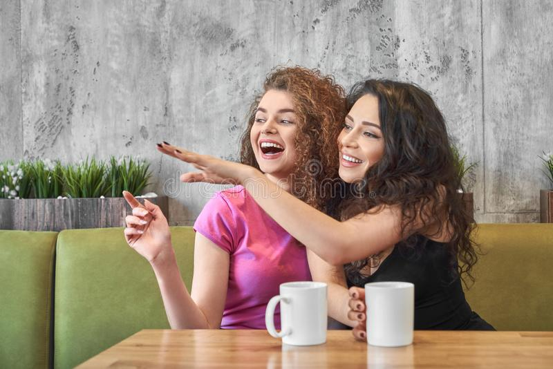 Young girls sitting in cafe and gossiping while drinking tea stock photos